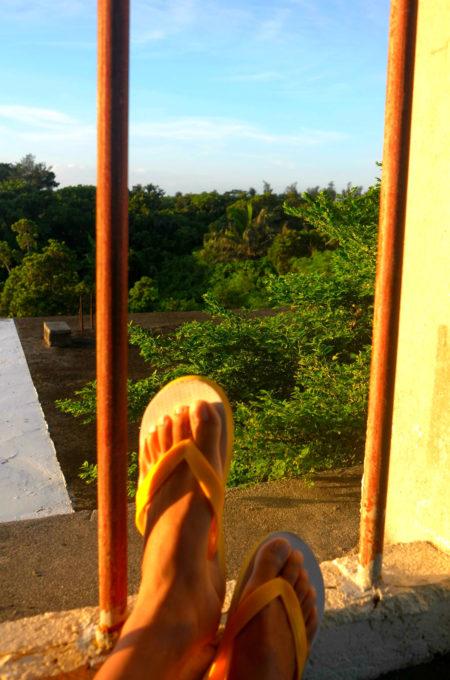 ビーチサンダルを履いた足とテラスからの眺め