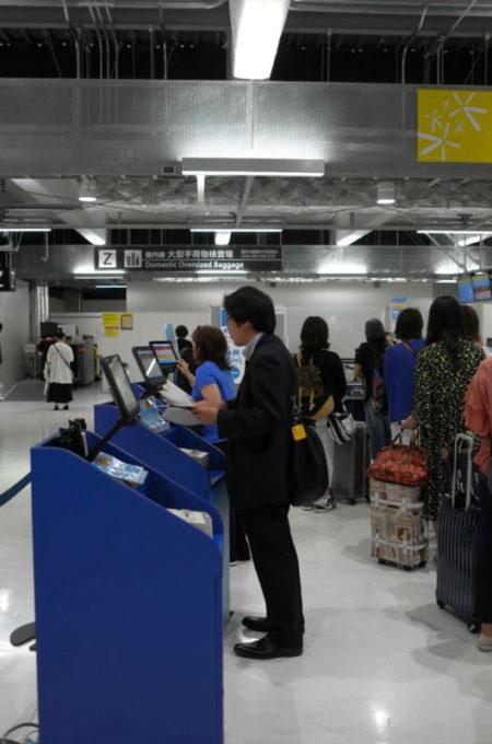 空港で搭乗券を発券する乗客
