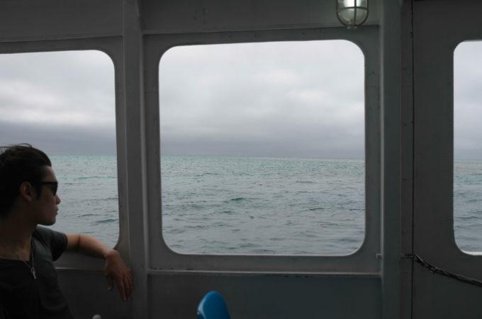船の中から海を眺める青年