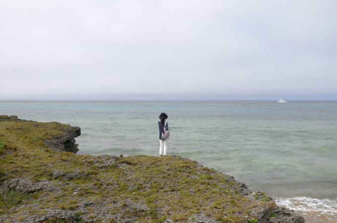 崖の上から海を見つめている女性