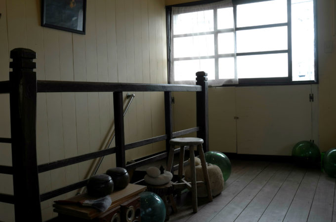 廊下に置かれた、碁盤、ガラスの浮き、木のスツールなど
