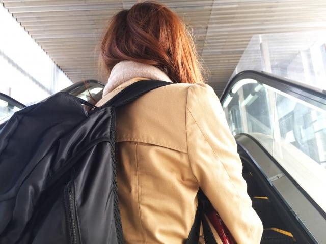 エスカレーターに乗って移動する旅人
