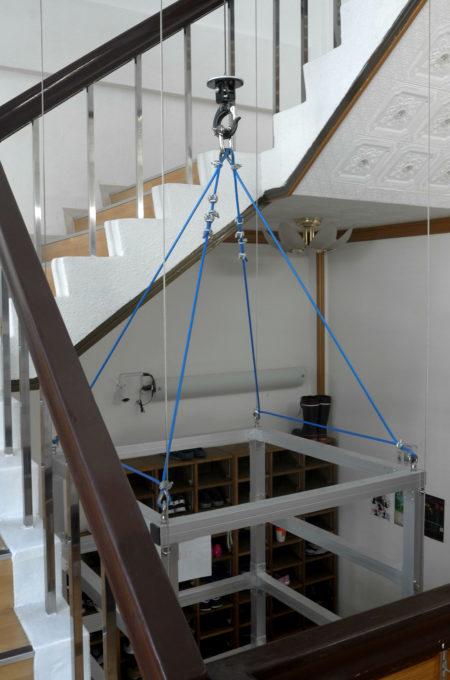螺旋階段の真ん中に吊るされた荷物用リフト