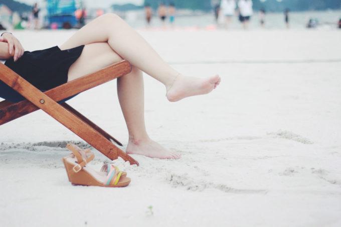ビーチでサンダルを脱いでチェアでくつろぐ女性