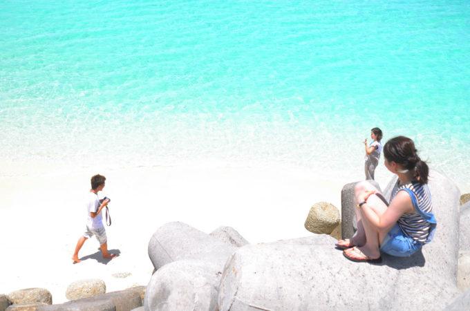 ビーチのテトラポットに座る女性