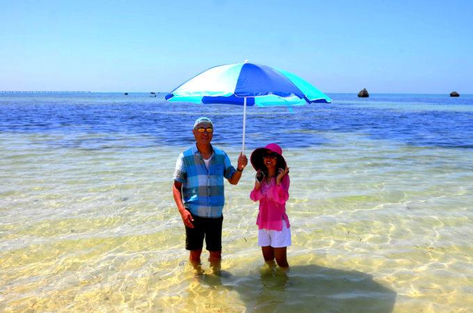 海の中で相合傘のカップル