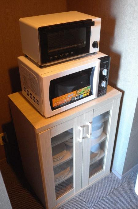 キッチンのトースターと電子レンジ、食器棚