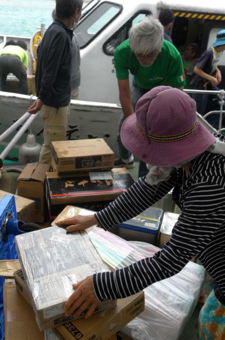 上原港で船から荷物を運び出す人たち