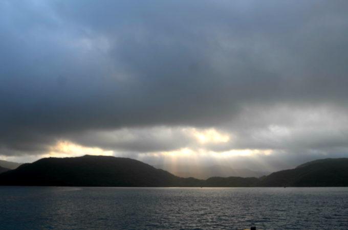 黒い雲の隙間から射す朝日