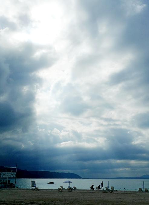 ビーチから見上げた曇天から薄く漏れる光の風景