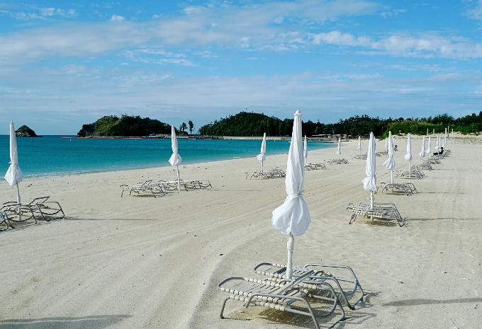 デッキチェアと畳まれたビーチパラソルが整然と並ぶビーチ