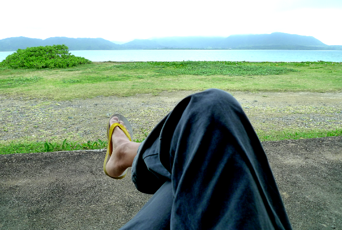 テラスのベンチに座って海を眺めるボランちゅ